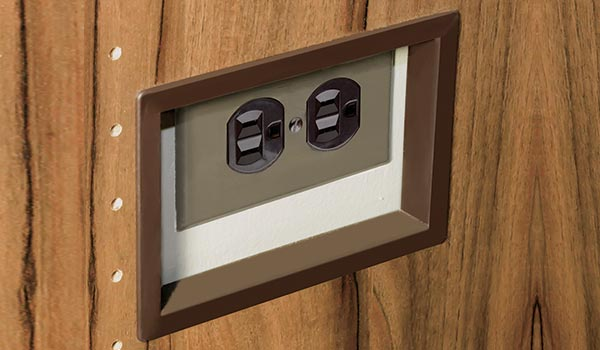 Plastic insert in brown to finish an electrical outlet cut-out