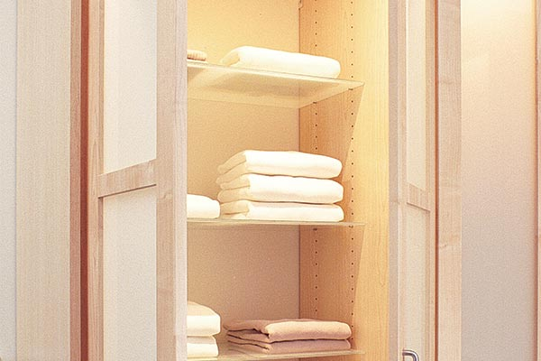 Adjustable glass shelves in custom wardrobe closet with drawers