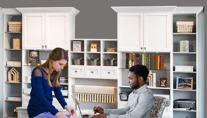 2 people working in an home office craft room combination space.