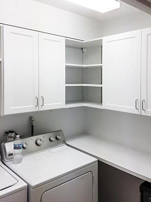 space saving laundry room design with cabinets for storage