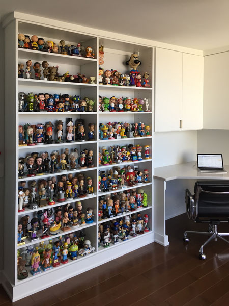Desk with collection of bobble heads on shelves