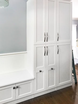 kitchenette pantry cabinets and custom bench seat with wainscotting