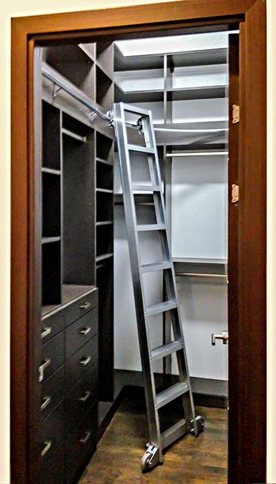 Small closet with rolling ladder to access storage near ceiling