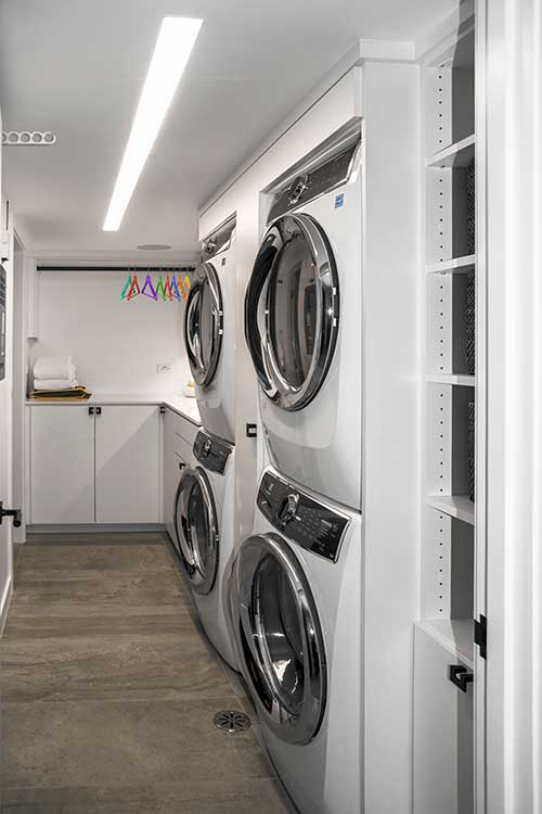 Long, narrow laundry room with corner sink and storage
