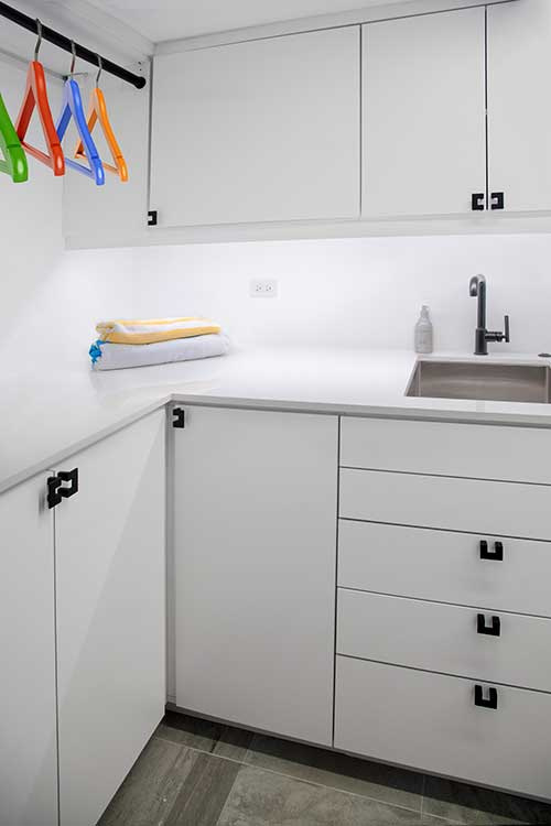 Laundry room cabinets with custom drawers that fit around basement pipes
