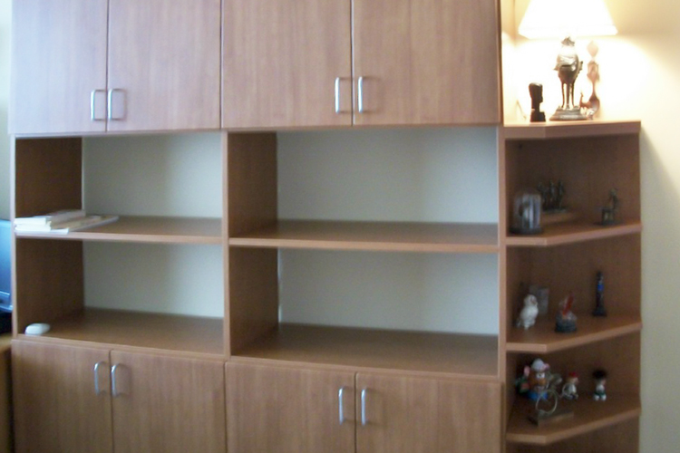 Custom home office wall units featuring bookshelves with angled shelves on the corners