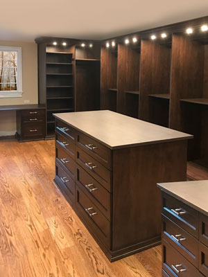 his and her walk-in closet with custom lighting and double island dressers