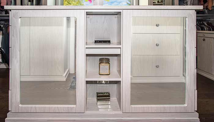 Closeup of a closet island with mirrors and shelves