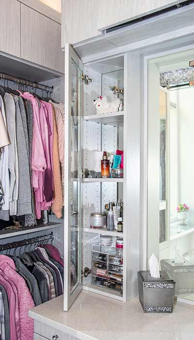 Closet vanity storage tower with mirror backed cabinet and glass doors