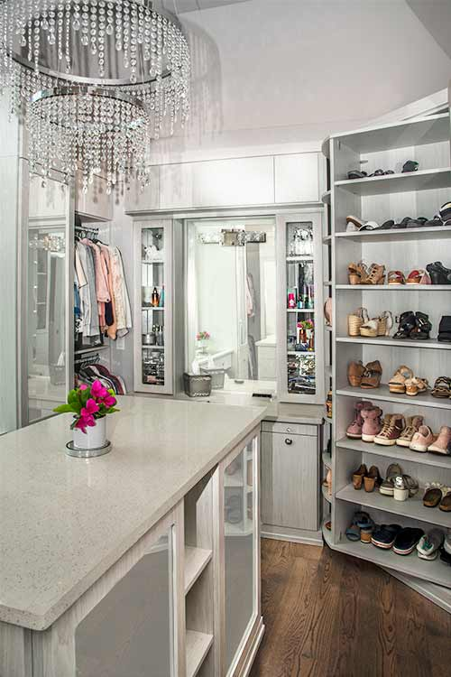 Walk-in closet with mirror doors on cabinets