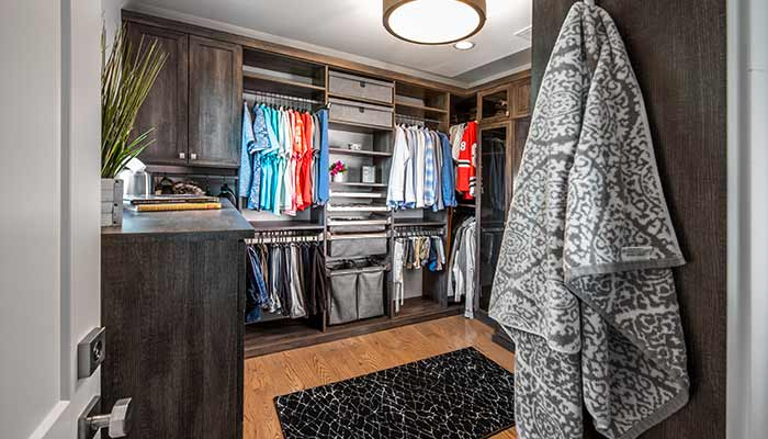 View of a custom mans walk-in closet from the doorway