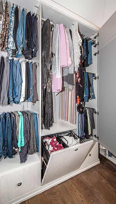 Closet with built-in hamper and cabinets with slide out pant racks