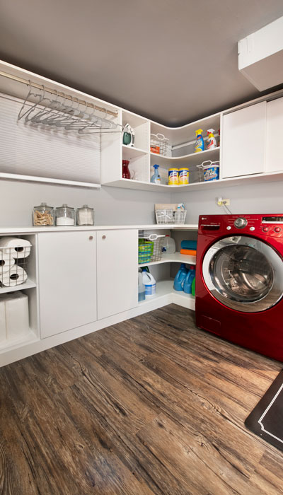 Basement laundry room with drying rod for drip-dry needs.