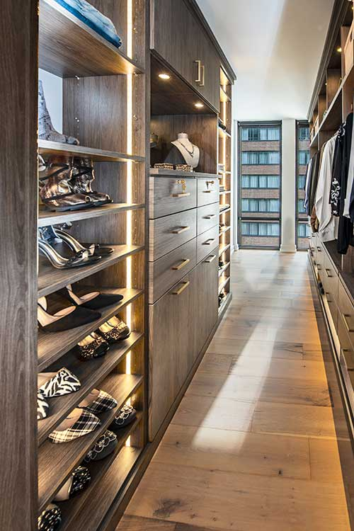 Galley style walk through closet with closet lighting system