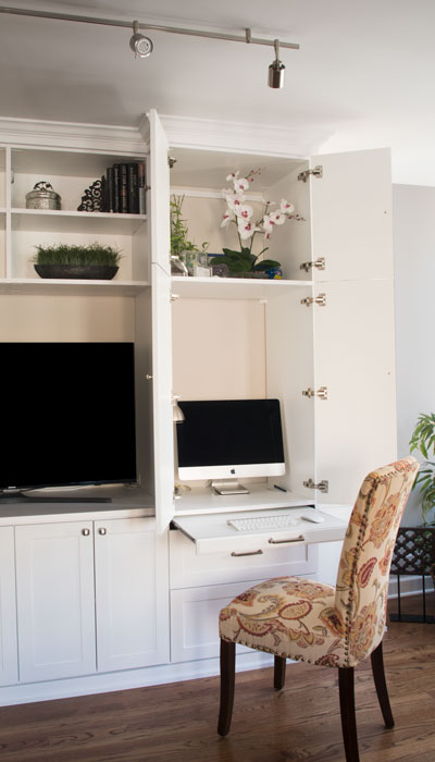 wall unit with desk has cabinets that open for desktop computer