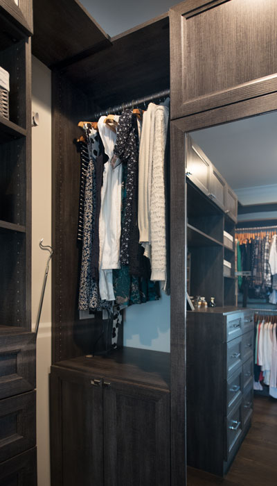Walk-through closet with mirrored closet door to conceal a steamer unit