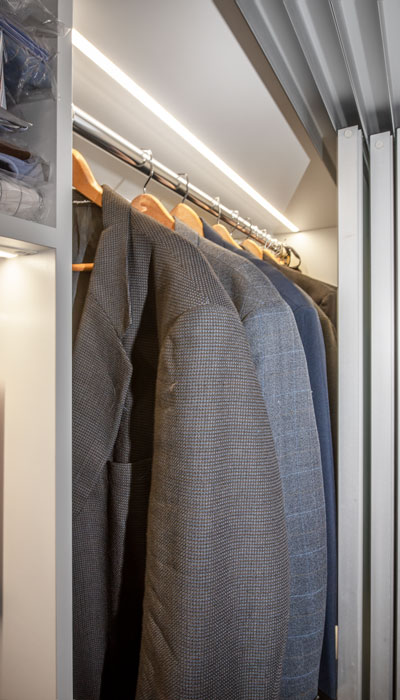 This reach-in closet is full of small closet lighting ideas.