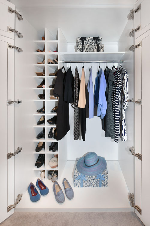 Custom reach-in closet with lighting and shoe cubbies