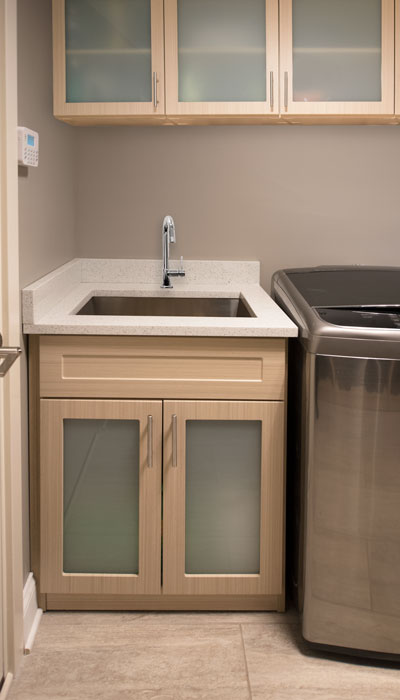 Laundry room sink cabinet with overhead storage cabinet uppers