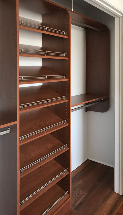 Reach-in closet with slanted shoe shelves for organizing footwear