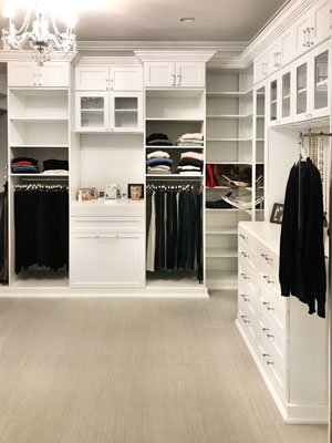 custom master closet with glass inserts and wood drawer faces