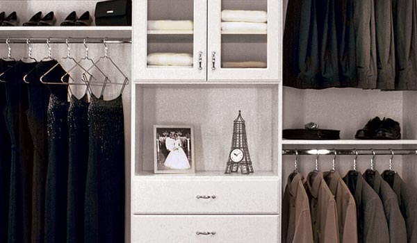 custom reach in closet design with hutch and glass doors